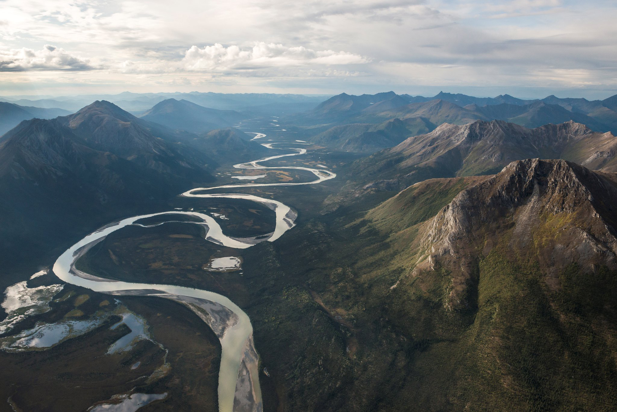 A river meanders through the treeless slopes of the Arctic Divide near the Nunamiut village of Anaktuvuk Pass. Gates of the Arctic National Park and Preserve.